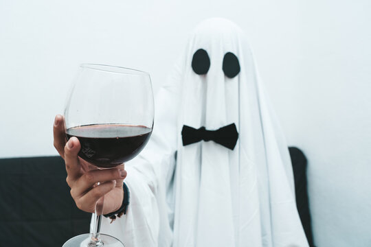 Detail of wine glass hold by a ghost during halloween