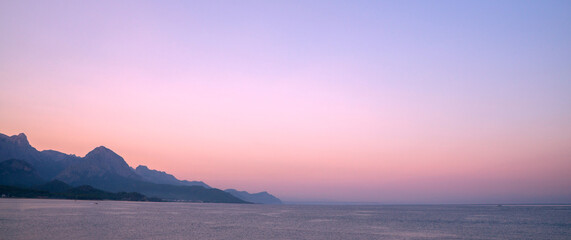 Pink dawn over the sea, mountains on the horizon in the air haze.