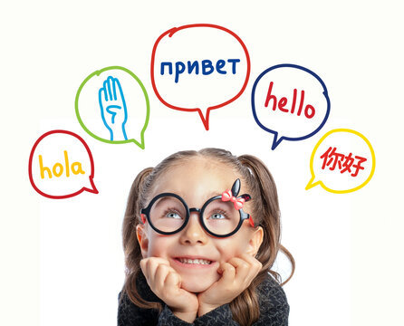 Beautiful cute little girl with eyeglasses looking at hello word in spanish, english, russian, chinese and american sign language in speech balloons. K-12 foreign language learning concept.