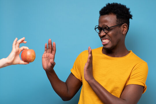 African young man rejecting apple isolated on blue background. Wrong diet concept.