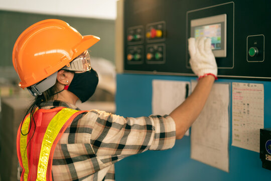Professional Industrial worker operate screen panel of heavy machine to setting a mechanic controller in factory atmosphere, Technician female engineer with safety wear and face mask in heavy factory.