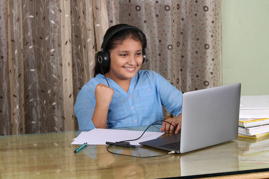 Young Indian girl wearing headset learning through laptop. E- learing concept.