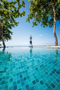 An Asian woman doing yoga exercises on the edge of an infinity swimming pool next to the sea, Indonesia, Southeast Asia