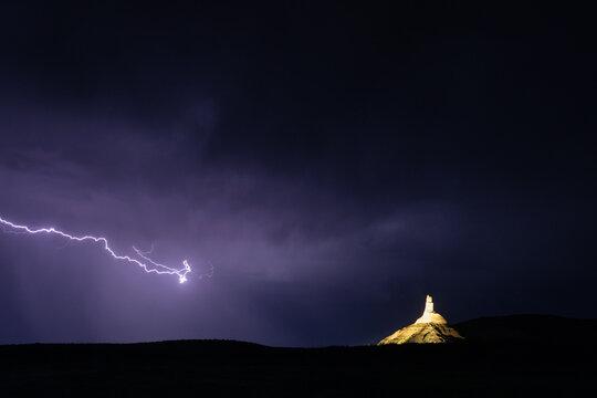 Lighting strike in a purple night sky over Needle Rock in Nebraska