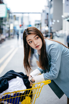 Young and fashionable asian girl pushed grocery cart in supermarket