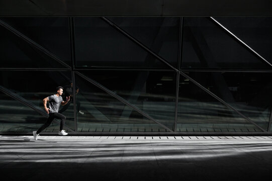 Male runner runs in city beside a glass architecture