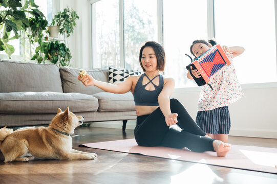 Asian young mom and daughter practicing yoga at home