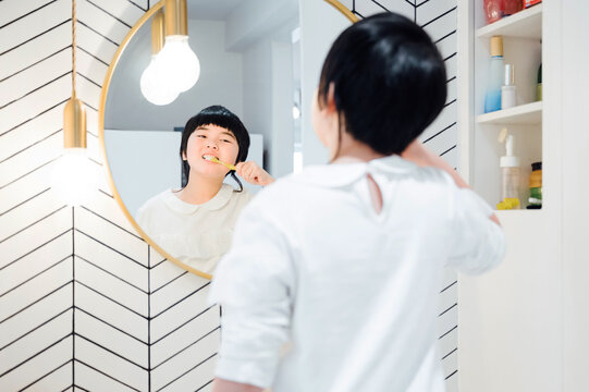 Cute little girl brushing her teeth at home