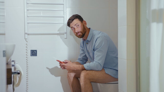 Happy businessman use phone sitting on the toilet smiling mobile restroom smartphone internet home bathroom close up slow motion