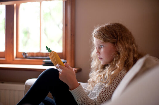 Young girl sitting on the sofa using her tablet