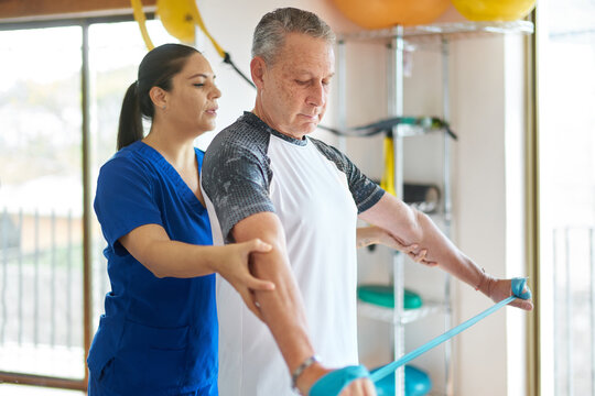 Senior man at a rehab clinic receiving exercise instructions from trainer