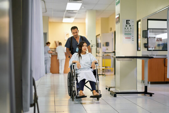Young woman in a wheelchair in a hospital with staff around