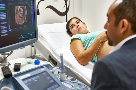 obstetrician doctor doing an ultrasound exam of a pregnant woman