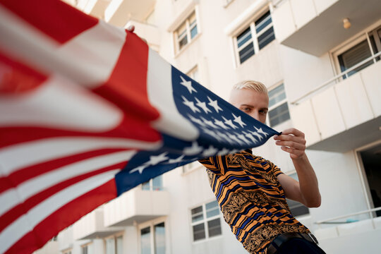 Stylish blond man with an american flag in hand