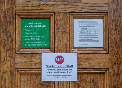 Signs on the front door of the Main Street School late elementary school in Irvington, NY detailing COVID-19 guidelines and restrictions