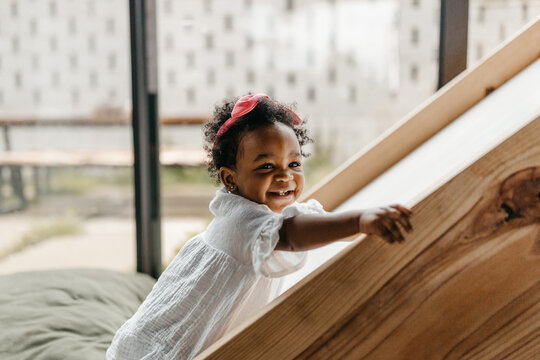 A cute little toddler girl crawling around the house / on an indoor slide.