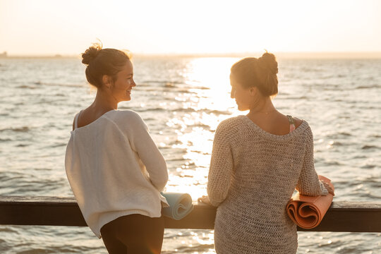 Pensive pleased friends talking while resting after fitness training on shore at dusk