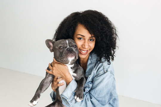 A studio portrait of an African American woman with beautiful curly hair holding a french bulldog.