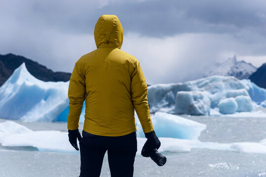 Photographer with a yellow jacket surrounded by some ice floes in Grey Lake, Patagonia, Chile