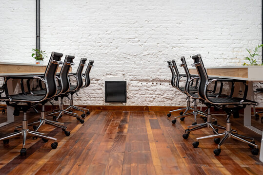 Chairs lined up at table in empty coworking space