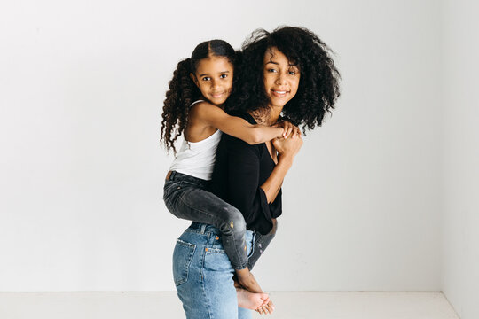A studio photograph of an African American mother giving her daughter a piggyback ride.