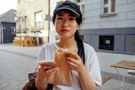 Young Woman Eating Baked Good On The Street