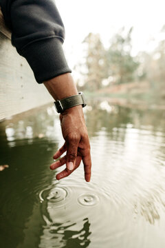 A hand creating a ripple effect in the water