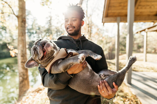 An African American man holding his french bulldog.