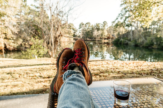 First person view of feet propped up on a table with a glass of wine.