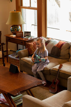 Young Child Learning to play Guitar Video Video Chat sitting in Living Room