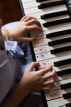 Close up on Hands of young child on Keyboard of piano