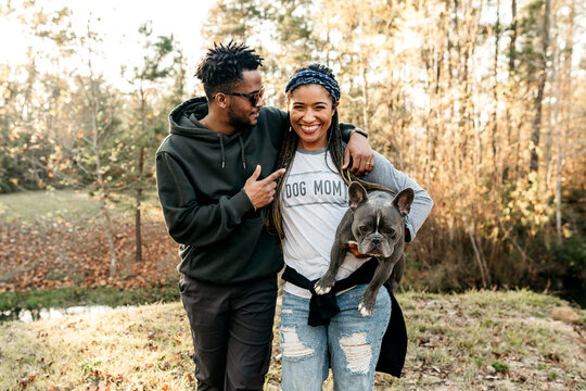 An African American couple walking out in nature with their french bulldog.
