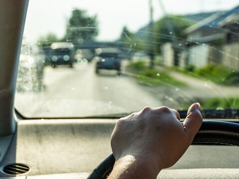 a woman's hand on the steering wheel, behind a dirty windshield, the outskirts of the village, selective focus