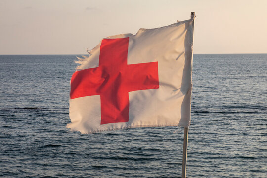 A white flag with a red cross flies over the beach at the resort against the sea