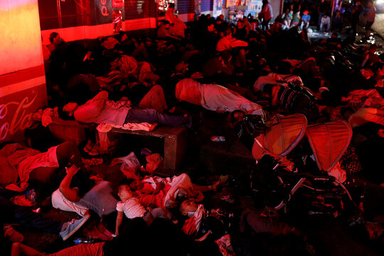 U.S.-bound Honduran migrants sleep on the floor after a long day of walking in Entre Rios