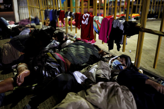 Honduran migrants sleep on the floor after a long day of walking in Entre Rios