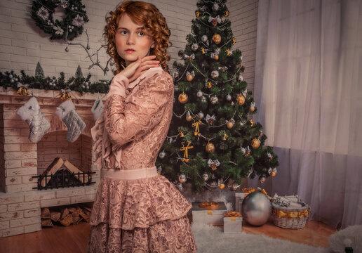 Das hübsche Mädchen vor dem Kamin und dem Weihnachtsbaum