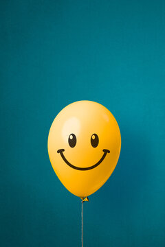 Stock photo of a yellow balloon with smiley face on a blue background