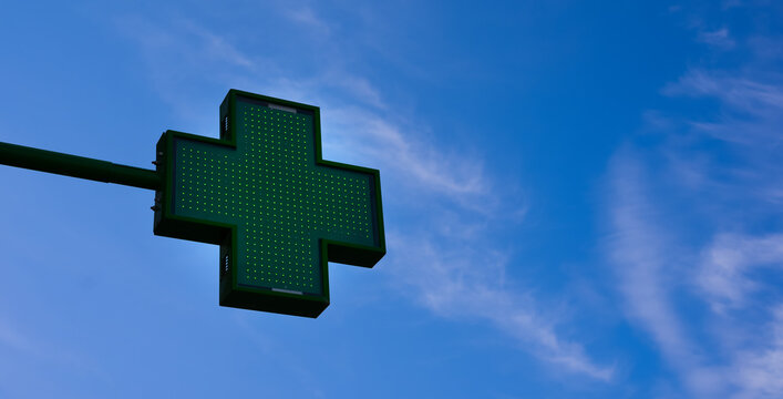 From a low angle you can see a green pharmacy cross on a pole with a blue sky in the background