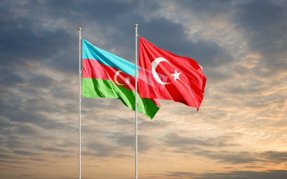 Azerbaijan and Turkey flags waving in the dawn sky. Symbol of international agreement and support during Karabakh war conflict with Armenia.