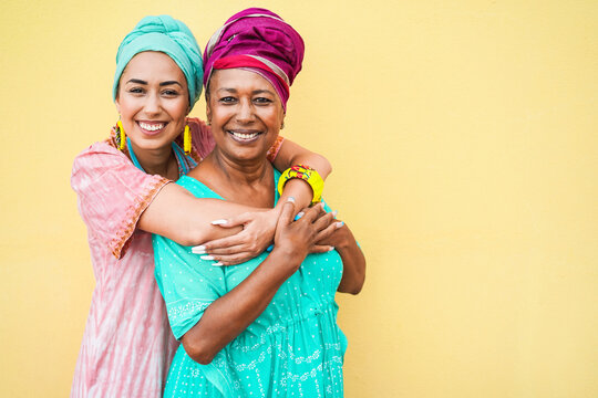 Happy mother and daughter with traditional african dresses smiling on camera - Focus on faces
