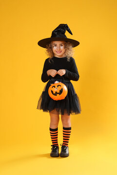Cute little girl with pumpkin candy bucket wearing Halloween costume on yellow background