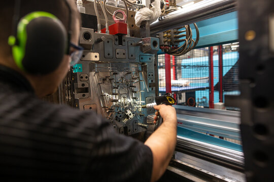 Technician freezing a mold for molding plastic in a plastic factory, industry concept