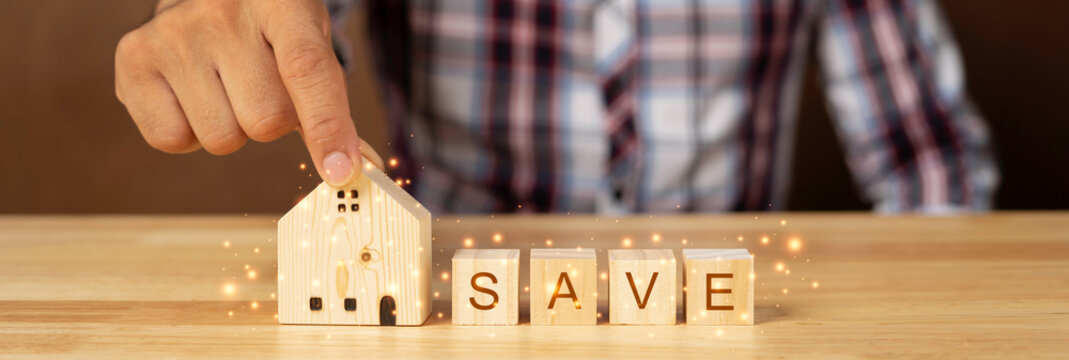 "A man's hand was holding a small wooden house and A wooden cube with the letters ""save"", the house concept is a safe place."