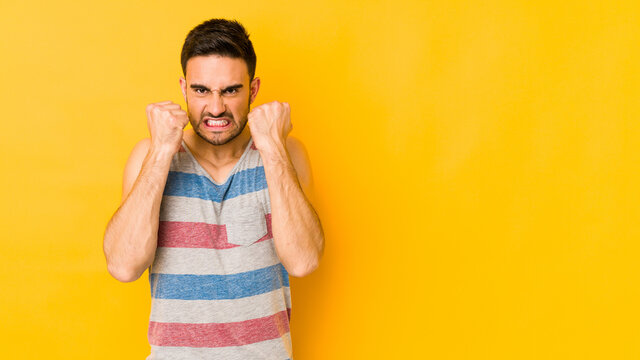 Young caucasian man isolated on yellow bakground showing fist to camera, aggressive facial expression.