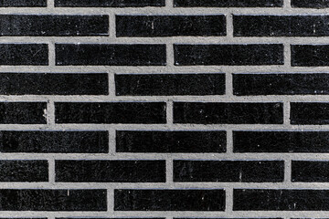 The black glossy brick wall of a modern apartment building. Modern nordic architecture. Pattern of...