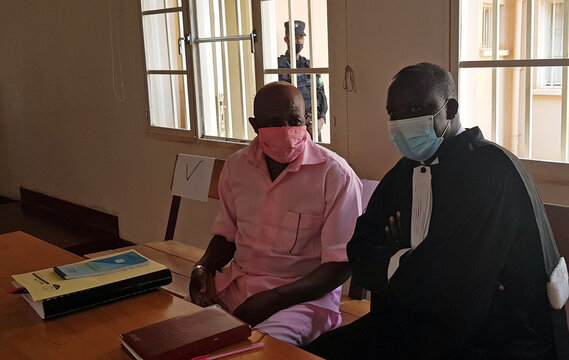 Paul Rusesabagina, sits with his lawyer inside the courtroom in Kigali