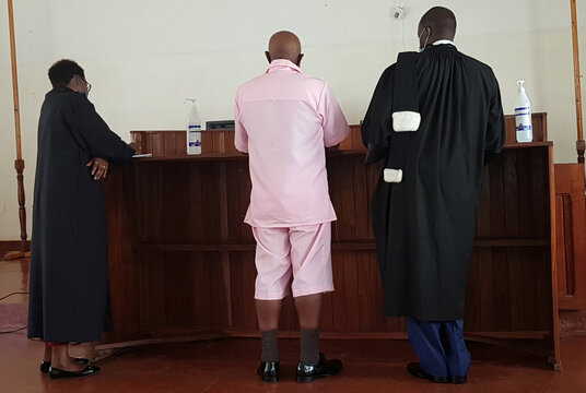 Paul Rusesabagina stands with his lawyers inside the courtroom in Kigali