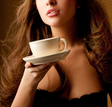 Coffee. Beautiful Girl Drinking Tea or Coffee. Cup of Hot Beverage. Young pretty woman drinking coffee. Morning.