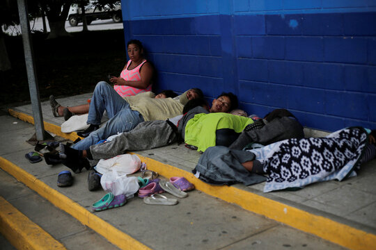 Hondurans sleep on the ground at the Corinto border crossing checkpoint between Guatemala and Honduras while trying to reach a migrant caravan towards the U.S., in Omoa